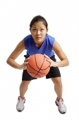 Young woman holding basketball, aiming for a hot - Asia Images Group