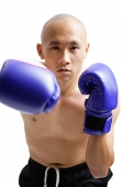 Young man wearing purple boxing gloves - Asia Images Group