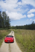 Red sports car on rural road - Asia Images Group