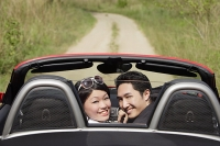 Couple in convertible sports car, turning to look at camera - Asia Images Group