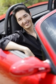 Man sitting in red convertible car, smiling at camera - Asia Images Group