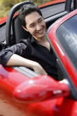 Man sitting in red convertible car, smiling - Asia Images Group