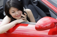 Woman sitting in convertible, looking at herself in side view mirror - Asia Images Group