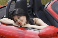 Woman sitting in red sports car, smiling at camera - Asia Images Group