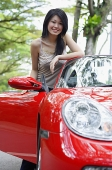 Woman standing next to red sports car - Asia Images Group