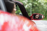 Woman in red sports car, reflected in side view mirror - Asia Images Group