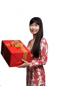 Woman with long straight hair, holding gift wrapped box - Asia Images Group