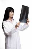 Woman in lab coat, looking at X-ray - Asia Images Group