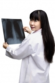 Female doctor with X-ray, looking over shoulder - Asia Images Group