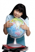 Woman embracing globe, smiling - Asia Images Group