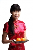 Woman in Cheongsam, holding plate with two oranges - Asia Images Group