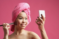 Woman pink turban, applying make-up - Asia Images Group