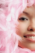 Woman with pink feathers around her face, cropped image - Asia Images Group