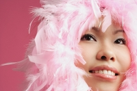 Woman's face surrounded by pink feathers - Asia Images Group