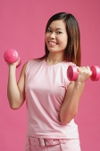Woman dressed in pink, standing against pink wall, holding dumbbells - Asia Images Group