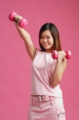 Woman dressed in pink, using dumbbells - Asia Images Group