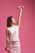 Woman dressed in pink, lifting dumbbell - Asia Images Group