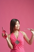 Woman in pink dress, holding champagne bottle and champagne glass - Asia Images Group