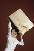 Woman holding big gift wrapped box - Asia Images Group