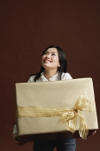 Woman holding gold gift wrapped box - Asia Images Group