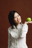 Woman holding green apple in palm of hand - Asia Images Group