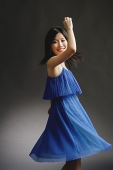 Woman in blue dress, spinning - Asia Images Group