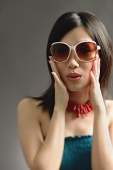 Woman wearing large sunglasses, hands on face - Asia Images Group