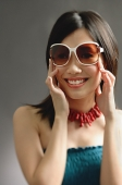 Woman wearing large sunglasses, smiling at camera - Asia Images Group