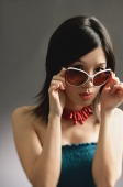 Woman adjusting large sunglasses, looking at camera - Asia Images Group