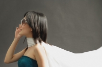 Woman wearing large sunglasses, tube top and scarf, looking away - Asia Images Group