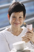 Mature woman with mobile phone, looking at camera - Asia Images Group