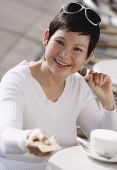 Mature woman in cafe holding out credit card - Asia Images Group