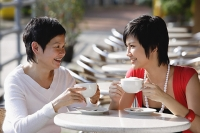 Two women in cafe having a drink - Asia Images Group