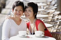 Mother and adult daughter in cafe, smiling at camera - Asia Images Group