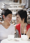 Mother and adult daughter in cafe, smiling at each other - Asia Images Group