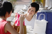 Two women at cafe, looking at items from their shopping bags - Asia Images Group