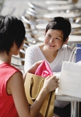 Two women at cafe, with shopping bags - Asia Images Group