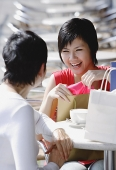 Two women at cafe with shopping bags, over the shoulder view - Asia Images Group
