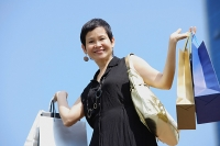 Mature woman carrying shopping bags, smiling at camera - Asia Images Group