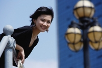 Woman leaning over railing, smiling at camera - Asia Images Group
