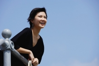 Woman leaning on railing, smiling, looking away - Asia Images Group