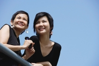 Women side by side, smiling, looking away - Asia Images Group
