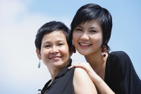 Women side by side, smiling, looking at camera - Asia Images Group