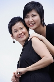 Mother and adult daughter smiling, looking at camera - Asia Images Group