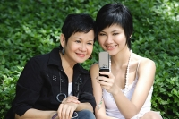Women side by side, smiling, looking at mobile phone - Asia Images Group