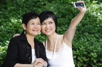 Women side by side, smiling, taking a picture with mobile phone - Asia Images Group