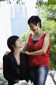 Mother and adult daughter looking at each other - Asia Images Group