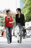 Mother and adult daughter walking in city, carrying shopping bags - Asia Images Group