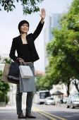 Woman in city, holding shopping bags, flagging cab - Asia Images Group