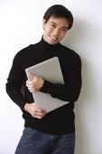 Man hugging laptop, laughing - Asia Images Group